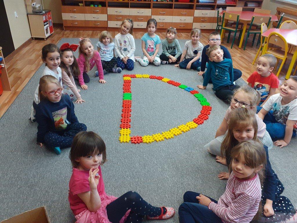 Dzieci z grupy przedszkolnej Słoneczka siedzą w kole na szarej wykładzinie. Pośrodku ułożono literkę D z kolorowych klocków.