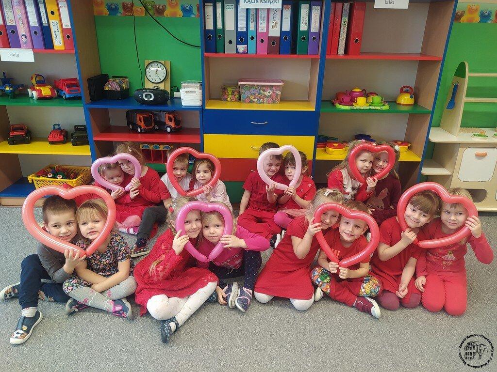 Dzieci z grupy przedszkolnej siedzą na dywanie w parach. Każda para dzieci trzyma balon w kształcie serduszka.