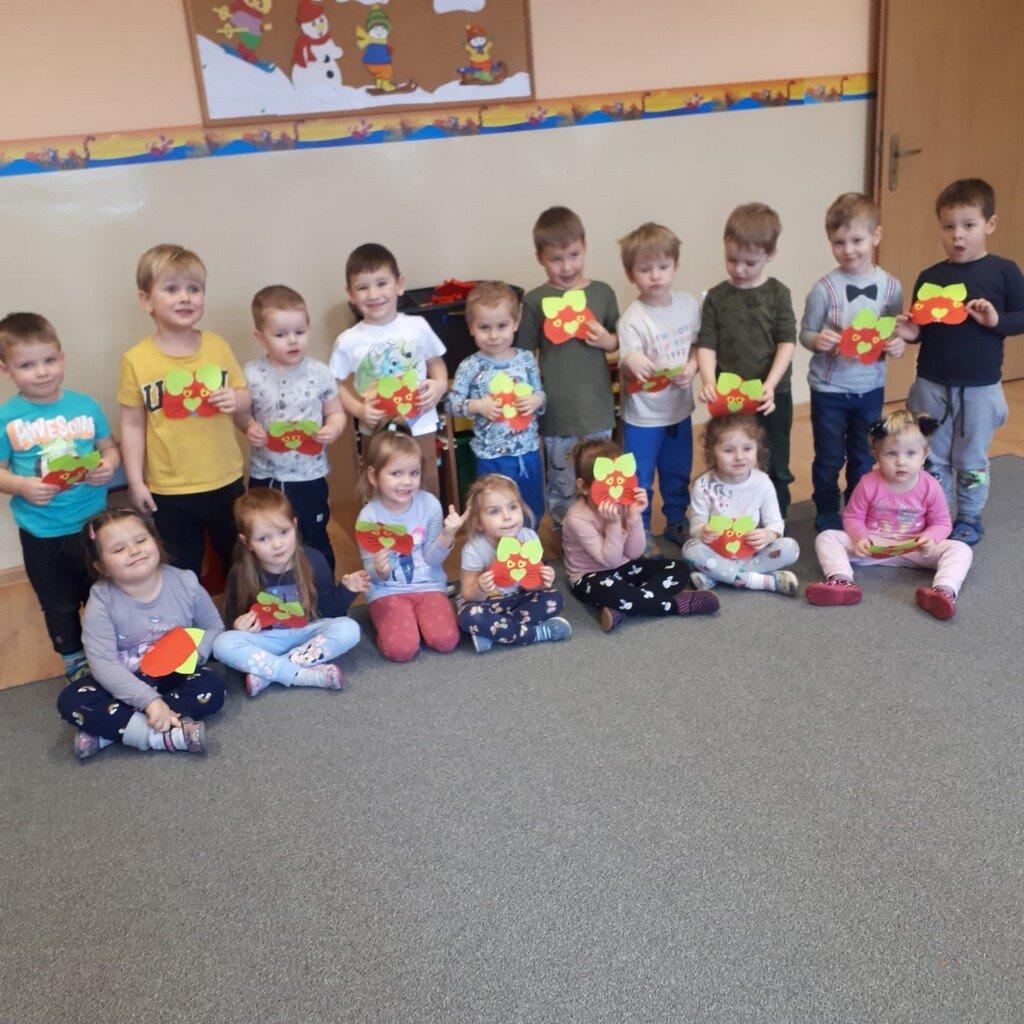 Grupa przedszkolna dzieci w sali przedszkolnej. Na ścianie zimowa gazetka, a podłodze szara wykładzina. Dzieci ustawione w dwóch rzędach, dziewczynki siedzą przez stojącymi za nimi chłopcami. Każde dziecko trzyma w ręku samodzielnie wykonane serduszko.