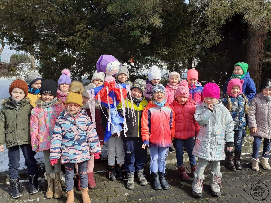 Grupa dzieci stojąca z Marzanną na podwórku.