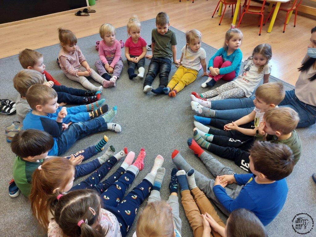 """Dzieci z grupy """"Biedronki"""" pokazują swoje dwie różne skarpetki."""